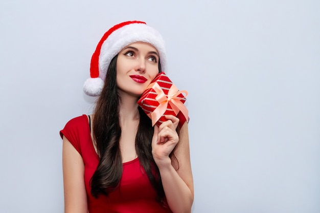 Close up christmas photo of dreaming woman with gift box in red dress and santa hat.