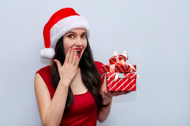 Close up christmas photo of impressed girl screaming wow omg with gift boxes in red dress and santa hat.