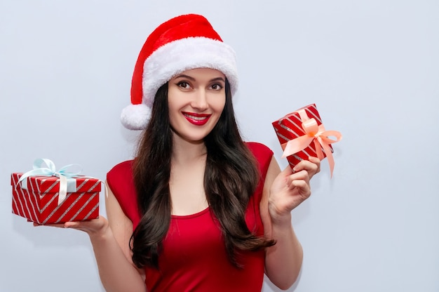 Close up christmas photo of smiling woman with gift boxes in red dress and santa hat.