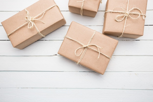 문자열로 묶여 크리스마스 스타일 소박한 갈색 종이 패키지를 닫습니다. 흰색 나무 배경입니다.