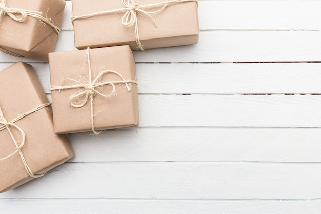 ひもで縛られたクリスマススタイルの素朴な茶色の紙のパッケージを閉じます。白い木の背景。