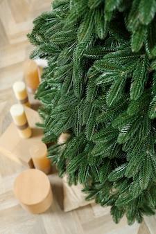 Елка крупным планом без игрушек. новогоднее настроение. зеленые ветви елки с подарками и свечами