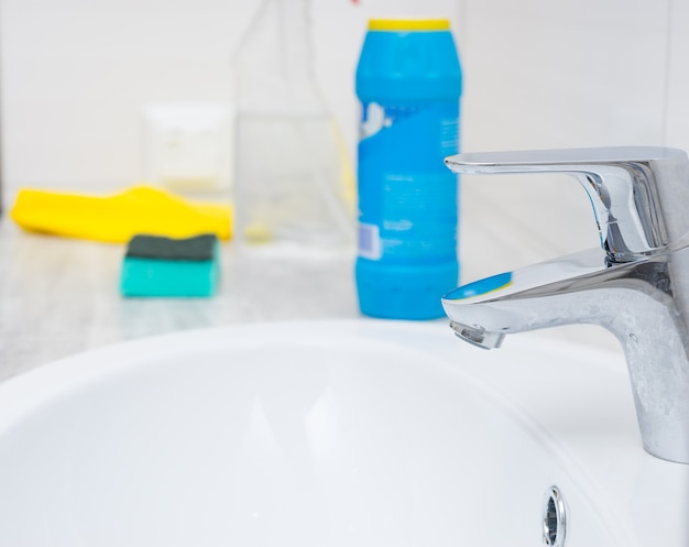 Close up of chrome sink spigot and cleaning chemicals, bottle, sponge and yellow rag with copy space