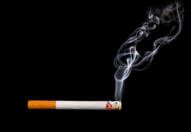 Close up of a cigarette with smoke showing at black background
