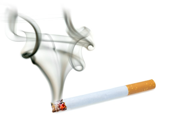 Close up of a cigarette with smoke showing at white background