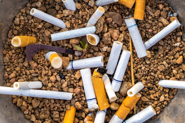 Close up of cigarettes butts in metal ashtray on street. concept of many cigarette debris after smoking.