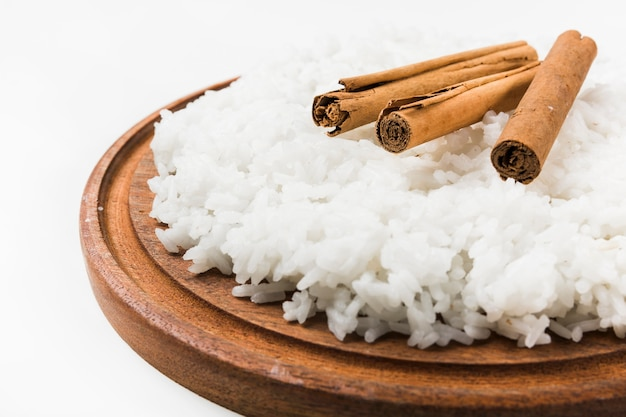 Close-up of cinnamon sticks on cooked white rice over wooden plate