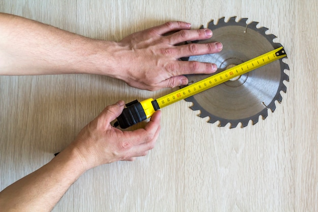 Close up of circular saw blade for wood work and worker hand with measuring tape on wood