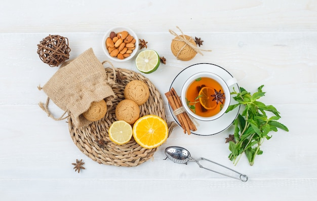 Close-up citrus fruits and cookies in wicker placemat with herbal tea and tea strainer,
