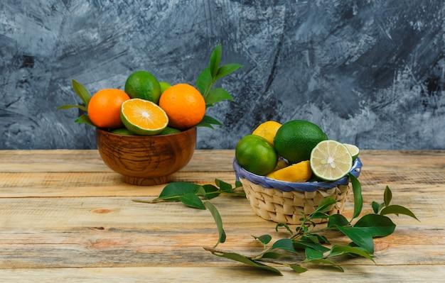 木の板に葉のあるボウルに柑橘系の果物をクローズアップ