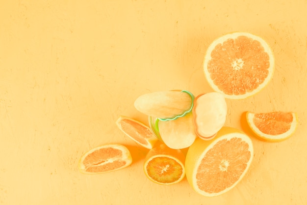 Close-up of citrus fruits with popsicles on yellow background