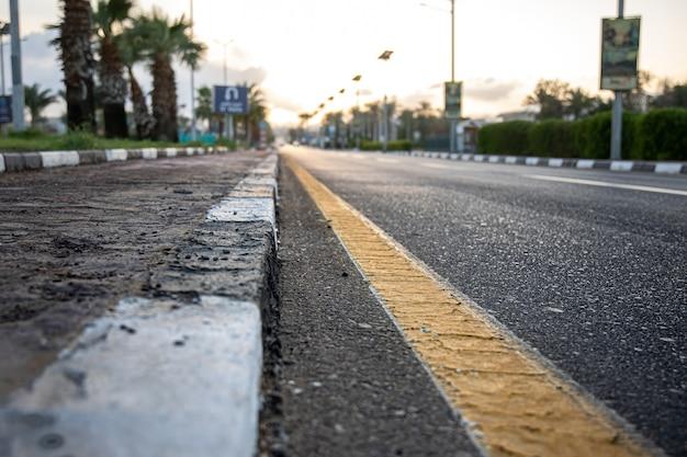 Закройте вверх по городской асфальтовой дороге с пальмами вдоль дороги на закате
