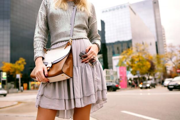 실버 스웨터, 실크 스커트, 고급 가죽 가방 및 선글라스를 착용하고 비즈니스 센터, 가을 봄 시즌 근처 뉴욕 거리에서 포즈를 취하는 세련된 우아한 여성의 도시 패션 세부 정보를 닫습니다.