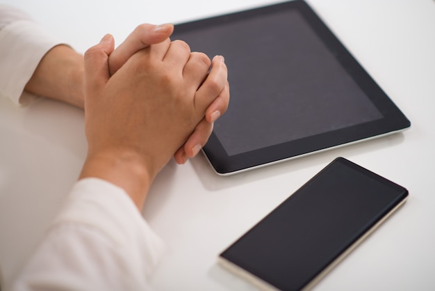 Close-up of clasped hands on table with pc tablet and smartphone