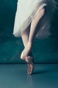 Ноги классической балерины крупным планом в пуантах на сером деревянном полу. проект балерины с кавказской моделью. концепция балета, танца, искусства, современности, хореографии