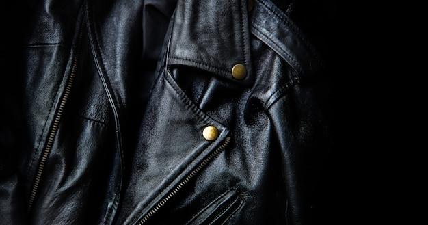 暗い背景のゴールドのボタンで古典的な黒革のジャケットを閉じる