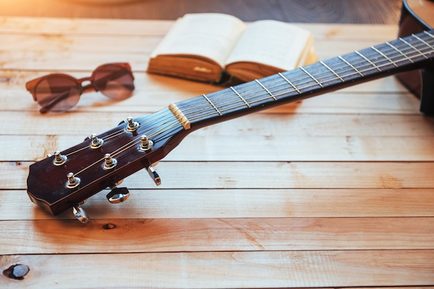 Close up classical guitar head with glasses and book