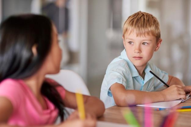 Primo piano di compagni di classe seduto alla scrivania