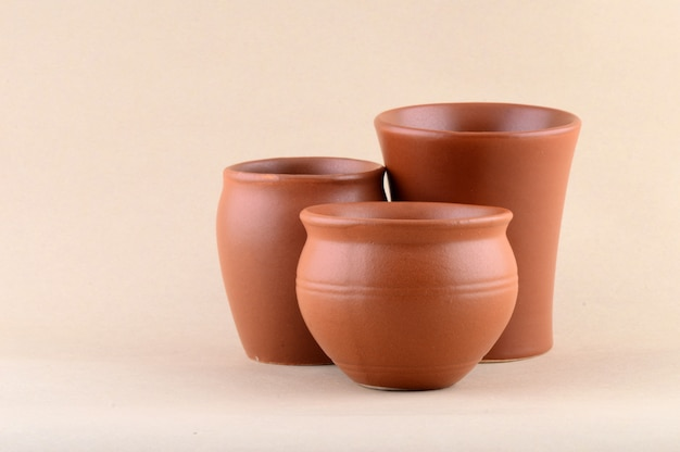 Close-up of clay pots on cream