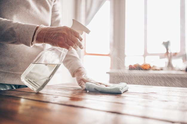 Close up of cleaning home wood table, sanitizing kitchen table surface with disinfectant antibacterial spray bottle, washing surfaces with towel and gloves
