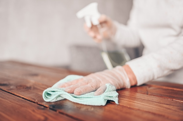 Close up of cleaning home wood table, sanitizing kitchen table surface with disinfectant antibacterial spray bottle, washing surfaces with towel and gloves.