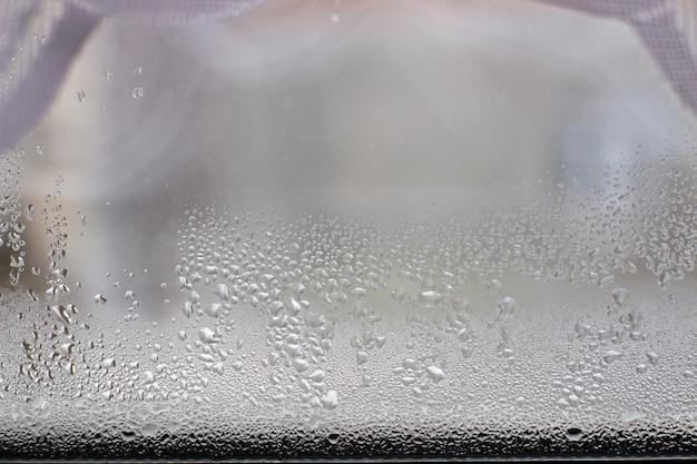 Крупным планом прозрачные капли воды на поверхности оконного стекла.