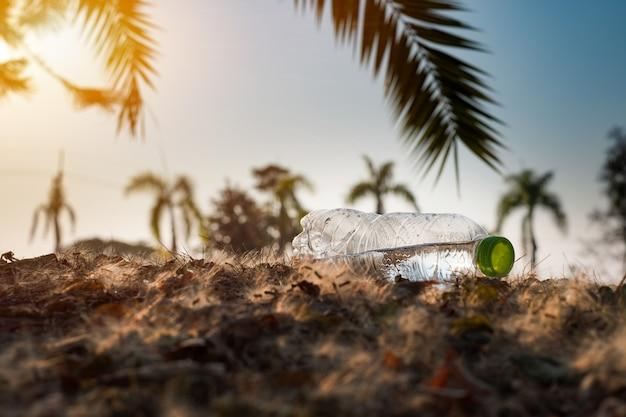 Закройте прозрачную пластиковую бутылку напитка с зеленой крышкой на дороге в парке