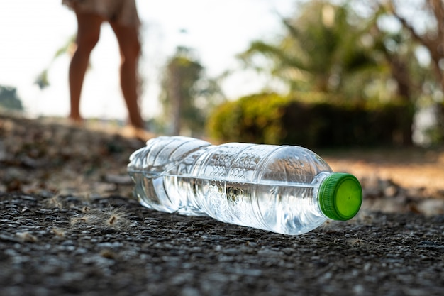 Close up clear plastic bottle water drink with a green cap on the road in the park at blurred background, trash that is left outside the bin