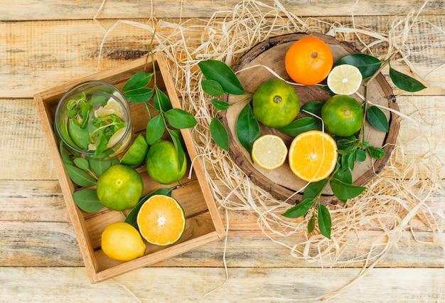 Clementine del primo piano in una cassa di legno con i mandarini sulla tavola di legno
