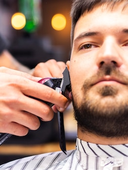 Close-up of client getting his sideburns cut