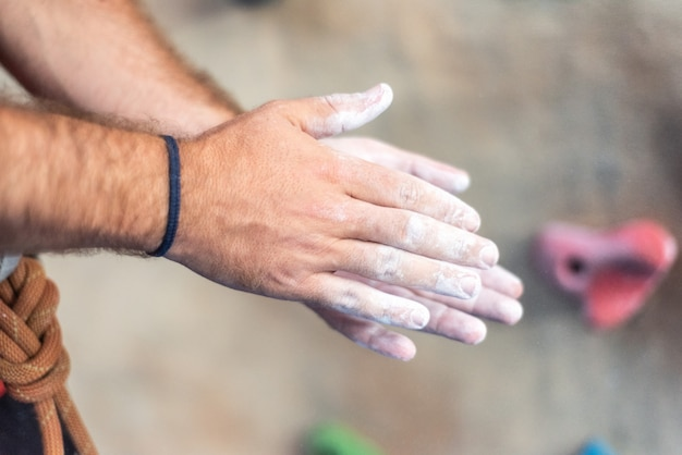 Close up of climber man coating hands in powder chalk magnesium