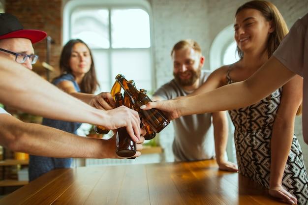 Крупный план звенящих пивных бутылок. молодая группа друзей пьет пиво, смеется и празднует вместе. женщины и мужчины с пивными бокалами. октоберфест, дружба, единение, концепция счастья.