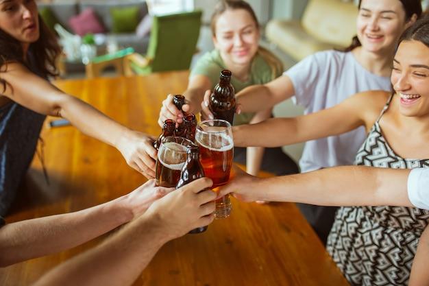 Закройте звон. молодая группа друзей пьет пиво, веселится, смеется и празднует вместе.