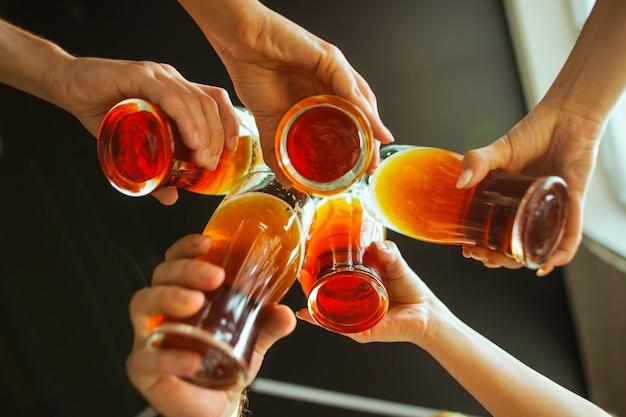 Звон крупным планом. молодая группа друзей пьет пиво, веселится, смеется и празднует вместе. женщины и мужчины с пивными бокалами. октоберфест, дружба, единение, концепция счастья.