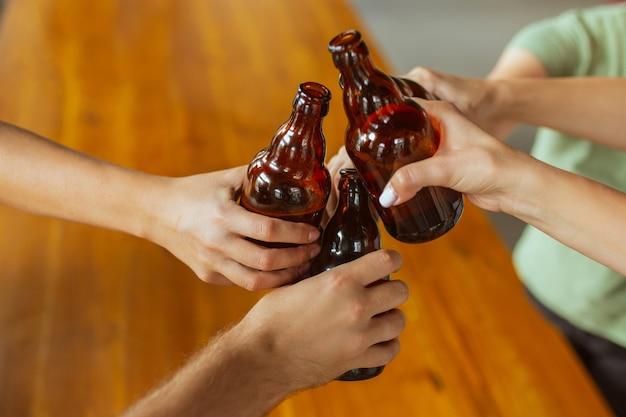 Крупным планом звон. молодая группа друзей пьет пиво, веселится, смеется и празднует вместе. женщины и мужчины с пивными бокалами. октоберфест, дружба, единение, концепция счастья.