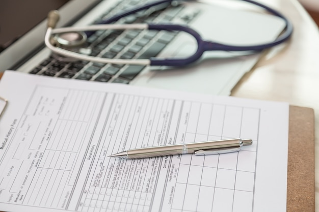 Close-up of clipboard with pen and stethoscope background