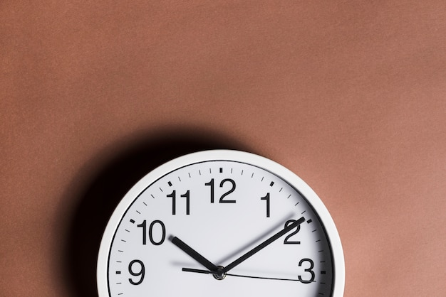 Close-up of clock against brown background