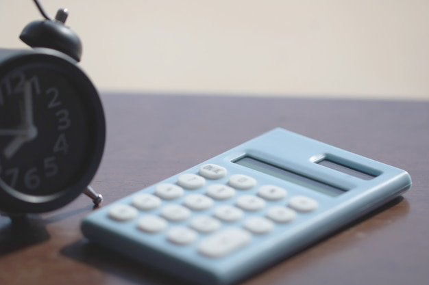 Close up clock and calculator on wood background business concept and tex time