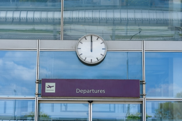 Close-up of a clock over closed glass airport doors with a departures sign
