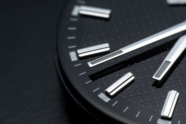 Close up clockwise on black clock face background. wristwatch in retro style
