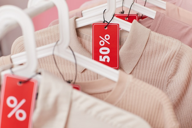 Close-up of clothes hanging on the rack with sale