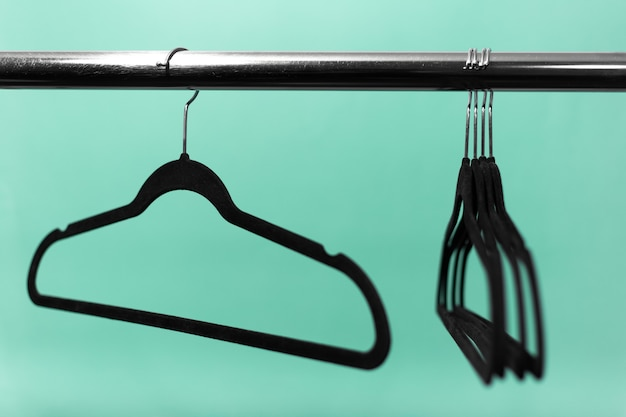 Close-up of clothes rack with black empty hangers on surface of aqua menthe color.