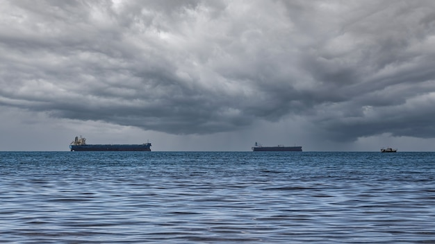 Close-up of a cloudy seascape on a rainy summer day. blue sea, storm clouds over the horizon, and several cargo ships.