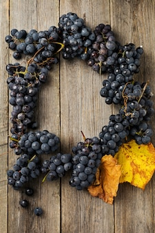 Close up of cluster blue grapes on old wooden
