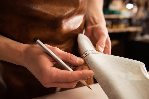 Primo piano di un calzolaio facendo misure per una scarpa