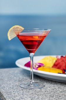 Close-up: the cocktail is cosmopolitan with a slice of lemon and next to it is a plate with exotic fruits: watermelons, pineapples, dragon fruit. beach party. pool party.