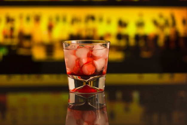 Close-up of cocktail with ice cubes at bar counter
