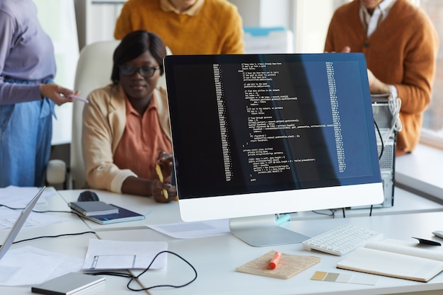 Close up of code on computer screen with diverse it development team working in background, copy space