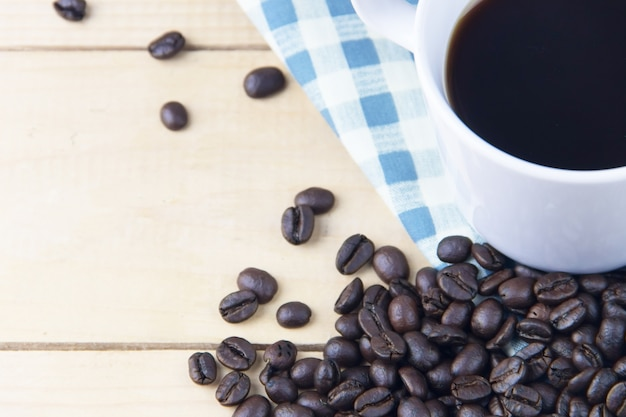 Close up coffee bean and hot black coffee in white cup on plain napkin