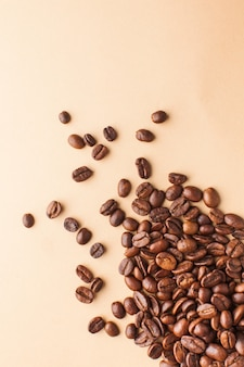 Close-up coffee beans are scattered in the lower corner on a light brown background. vertical photo with space for text. for roasters, coffee houses and cafes.